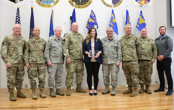 """In a ceremony April 6, 2019, Family Readiness volunteer Renee Kotch (center) is named 2018 Region 3 Volunteer of the Year at the 193rd Air Operations Group, State College, Pennsylvania. Maj. Gen. Tony Carrelli (right of Kotch), adjutant general, Pennsylvania National Guard, and other distiguished visitors, attended the event to congratulate Kotch on her efforts to provide support and resources to the families of the AOG. """"There is so much pride within this volunteer community. My advice to servicemembers: Don't assume your spouse doesn't want to be involved. Let us take the same passion, pride and patriotism we all share in our hearts and allow us - the family members - to serve, too,"""" Kotch said. (U.S. Air National Guard photo by Tech. Sgt. Denise Mckee)"""