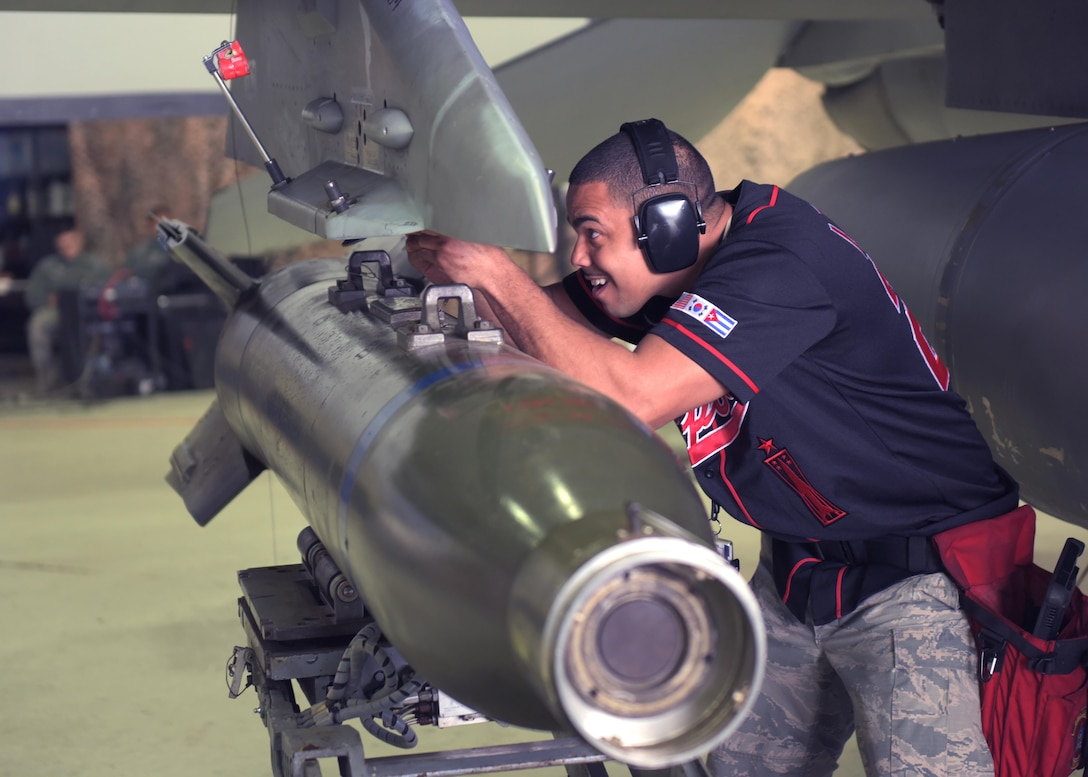 U.S. Air Force Staff Sgt. Marcel Leduff, a weapons load crew team chief assigned to the 51st Aircraft Maintenance Squadron, mounts an armament onto an F-16 Fighting Falcon during a weapons load crew competition at Osan Air Base, Republic of Korea, April 5, 2019. Weapons load crew competitions test a squadron's ability to safely and accurately load munitions onto their respective aircraft. (U.S. Air Force Photo by Staff Sgt. Timothy Dischinat)