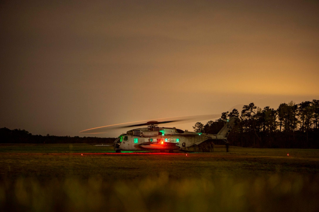 A helicopter sits on the ground at night with its lights on as two vehicles are loaded onto it.