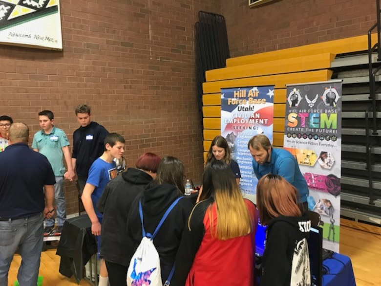 Students at Monument Valley High School in Kayenta, Utah, watch Hill Air Force Base electrical engineer Kristen Keyes and computer scientist Tyler Shilling conduct an experiment during the San Juan Career Fair March 27, 2019. Hill AFB computer scientists and engineers presented the electricity demonstration, taught some basic coding skills and encouraged students to focus on STEM-related subjects, giving them an idea of the important work they could do if they chose an Air Force career. (Courtesy photo)