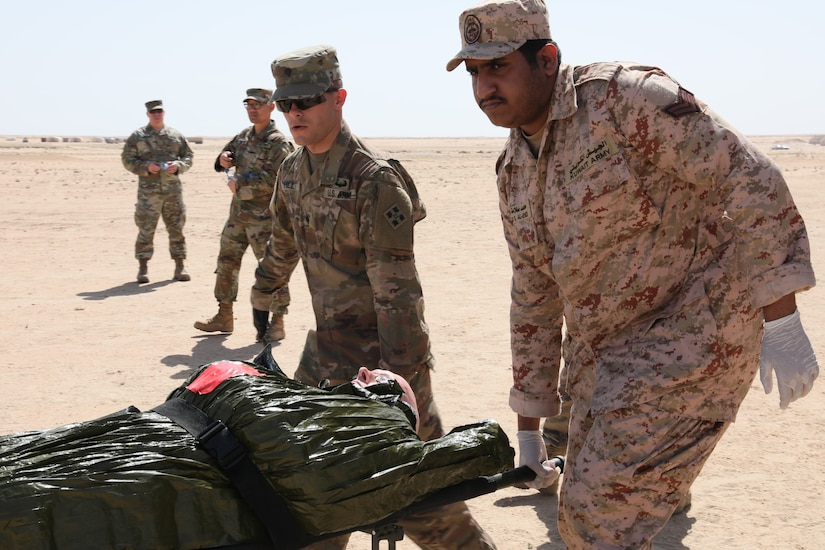 Spc. Hill of 1st Battalion, 68th Armor Regiment, 3rd Armored Brigade, 4th Infantry Division, left, and a Kuwait Land Forces soldier carry a simulated casualty to an aid station during a combined forces medical training event at the Udairi Training Range on April 2, 2019. The exercise simulated an oil rig explosion and prepared both U.S. and Kuwaiti troops, as well as Kuwaiti civilian medical professionals, to respond quickly in case of a wide-scale emergency.