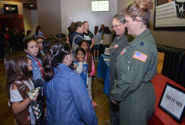 "Tech. Sgt. Debra Harper (left), 68th Airlift Squadron loadmaster, and Lt. Col. Kari Hill, 433rd Operations Support Squadron commander/pilot, talk to girls at the ""Marvelous Women Don't Need Capes"" event in the lobby of the Alamo Drafthouse movie cinema, March 23, 2019. The ""Show them Everything Possible"" Organization of San Antonio hosted the event."