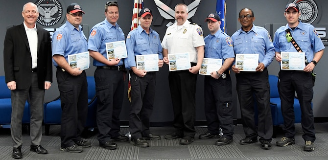 ": Rich Tighe, left, general manager for the AEDC Test Operations and Sustainment contract, recognizes Arnold Air Force Base Fire and Emergency Services team members March 8 for their response to a recent sandblasting incident when a TOS team member sustained an injury. Tighe presented certificates thanking the team for their ""responsiveness and decision-making"" which ""made a major difference in the life of one of our employees."" Also pictured from left, are Facility Support Services contract FE Services team members: Firefighter Crew Chief Kip Luttrell, Paramedic/Firefighter Cory Friend, Driver/Operator Ken Locker, Assistant Chief for Operations Gary Horn, Firefighter Justin Wiser, Firefighter T.A. King, Driver/Operator Brandon Gunn, and not pictured Driver/Operator Roger Whitton, Paramedic/Firefighter Brian Taylor and Driver/Operator Lonnie Brown. (U.S. Air Force photo by Jill Pickett)"