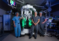 Surgeons stand next to the da Vinci Surgery System in an operating room.