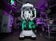 The da Vinci Surgery System sits in an operating room illuminated with colorful lights.