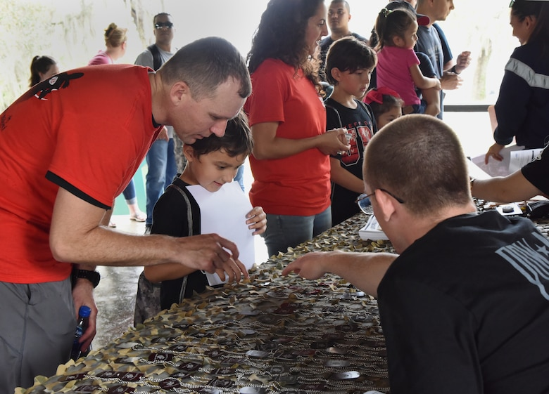U.S. Air Force Capt. Michael Blank, 81st Medical Operations Squadron nurse, helps his son, Carson, choose an event dog tag during Operation Hero at Keesler Air Force Base, Mississippi, April 6, 2019. The event, hosted by the Airman and Family Readiness Center in recognition of the Month of the Military Child, gave military children a glimpse into the lives of deployed military members. Children received Operation Hero dog tags and t-shirts as they made their way through the mock deployment line as well as the opportunity to experience medical triage demonstrations, gas mask training and have their faces painted. (U.S. Air Force photo by Kemberly Groue)