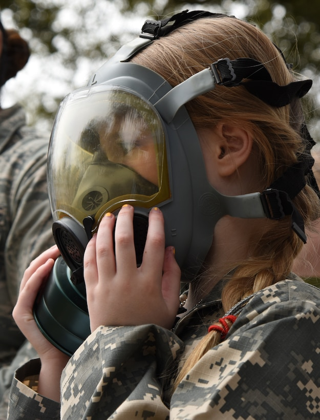 Emily Quigley, daughter of U.S. Air Force Col. Marcia Quigley, 81st Mission Support Group commander, tries on a gas mask during Operation Hero at Keesler Air Force Base, Mississippi, April 6, 2019. The event, hosted by the Airman and Family Readiness Center in recognition of the Month of the Military Child, gave military children a glimpse into the lives of deployed military members. Children received Operation Hero dog tags and t-shirts as they made their way through the mock deployment line as well as the opportunity to experience medical triage demonstrations, gas mask training and have their faces painted. (U.S. Air Force photo by Kemberly Groue)