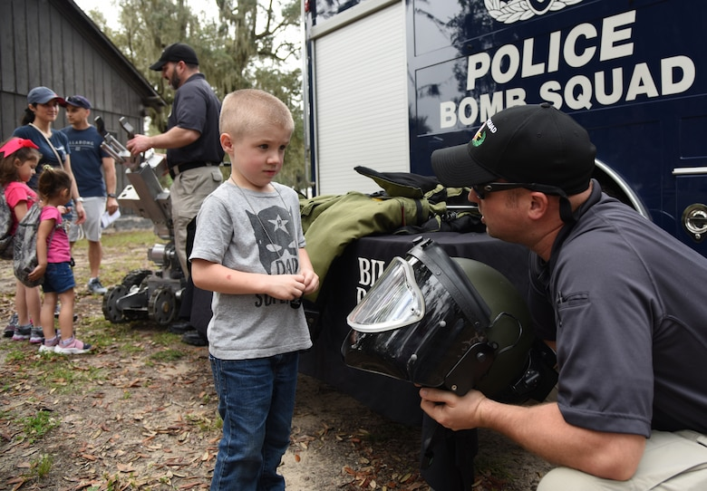 Sergeant Matthew Boone, Biloxi Bomb Squad technician, shows a protective helmet worn by his team members to Mason Taykowski, son of U.S. Air Force Tech. Sgt. Justin Taykowski, 338th Training Squadron instructor, during Operation Hero at Keesler Air Force Base, Mississippi, April 6, 2019. The event, hosted by the Airman and Family Readiness Center in recognition of the Month of the Military Child, gave military children a glimpse into the lives of deployed military members. Children received Operation Hero dog tags and t-shirts as they made their way through the mock deployment line as well as the opportunity to experience medical triage demonstrations, gas mask training and have their faces painted. (U.S. Air Force photo by Kemberly Groue)
