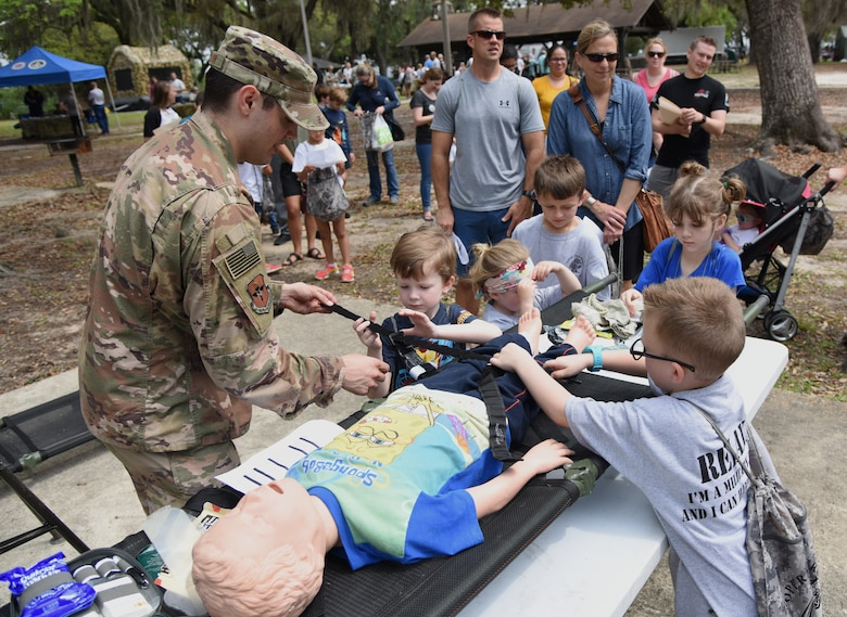U.S. Air Force Senior Airman Brock Mauldin, 81st Medical Support Squadron education and training self aid buddy care wing advisor, provides a medical triage demonstration to military children during Operation Hero at Keesler Air Force Base, Mississippi, April 6, 2019. The event, hosted by the Airman and Family Readiness Center in recognition of the Month of the Military Child, gave military children a glimpse into the lives of deployed military members. Children received Operation Hero dog tags and t-shirts as they made their way through the mock deployment line as well as the opportunity to experience medical triage demonstrations, gas mask training and have their faces painted. (U.S. Air Force photo by Kemberly Groue)