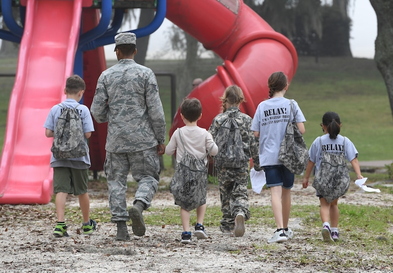 Military children are escorted to the next check list item during Operation Hero at Keesler Air Force Base, Mississippi, April 6, 2019. The event, hosted by the Airman and Family Readiness Center in recognition of the Month of the Military Child, gave military children a glimpse into the lives of deployed military members. Children received Operation Hero dog tags and t-shirts as they made their way through the mock deployment line as well as the opportunity to experience medical triage demonstrations, gas mask training and have their faces painted. (U.S. Air Force photo by Kemberly Groue)