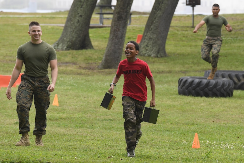 Carlos Cadet, Jr., son of U.S. Marine Corps Cpl. Jalisa Cadet, Keesler Marine Detachment administration clerk, runs through an obstacle course as he is escorted by Cpl. Davis Steiner, Keesler MARDET instructor, and followed by Pfc. Janathan Singh, Keesler MARDET student, during Operation Hero at Keesler Air Force Base, Mississippi, April 6, 2019. The event, hosted by the Airman and Family Readiness Center in recognition of the Month of the Military Child, gave military children a glimpse into the lives of deployed military members. Children received Operation Hero dog tags and t-shirts as they made their way through the mock deployment line as well as the opportunity to experience medical triage demonstrations, gas mask training and have their faces painted. (U.S. Air Force photo by Kemberly Groue)