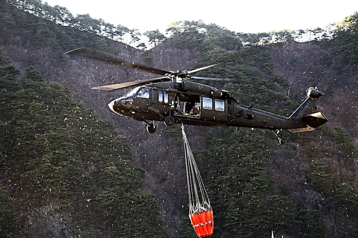 GANGWON, Republic of Korea – A UH-60 Black Hawk helicopter crew with 2-2 Assault Helicopter Battalion, 2nd Combat Aviation Brigade, 2nd Infantry Division/ROK-U.S. Combined Division, uses a Bambi bucket to drop water on the wildfire from the air in efforts to extinguish the blaze at Gangwon province, April 5. The effort is in partnership with Republic of Korea Army III Corps Command and other local agencies. (Courtesy photo by Republic of Korea Army Public Affairs)
