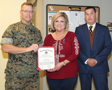 Shannon Baker receives the Meritorious Civilian Service Award for her performance while serving as Branch Head, Current Operations Branch, Maintenance Management Center, during a ceremony, April 5.