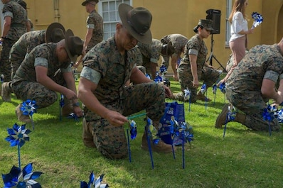 A drill instructor from Marine Corps Recruit Depot San Diego places pinwheels in a garden area during the Pinwheel Garden Event at MCRD San Diego, April 2.