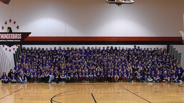 Students and staff gather for a group photo April 5, 2019, in Nathan Twining Elementary and Middle School on Grand Forks Air Force Base, North Dakota. The group photo was followed by a Month of the Military Child school rally, which included an awards presentation, band performance and ice cream social. (U.S. Air Force photo by Senior Airman Elora J. Martinez)