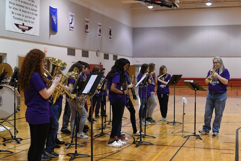 """Students in the school band are led in a rendition of Queen's """"We Will Rock You"""" during a rally April 5, 2019, in Nathan Twining Elementary and Middle School on Grand Forks Air Force Base, North Dakota. Students and staff gathered together for a Month of the Military Child celebration, which acknowledged all the children's hard work and rewarded them with an ice cream social. (U.S. Air Force photo by Senior Airman Elora J. Martinez)"""