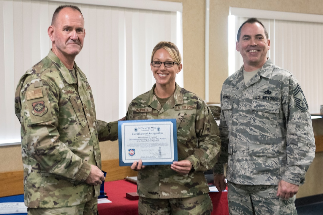 Senior Master Sgt. Larissa Caldwell is recognized during a ceremony April 7, 2019, by West Virginia Air National Guard Command Chief Master Sgt. David Stevens, left, and 167th Airlift Wing Command Chief Master Sgt. Troy Brawner, right, for her selection as  the Outstanding Airman of the Year in the senior non-commissioned officer category. (U.S. Air National Guard photo by Tech. Sgt. Jodie Witmer)