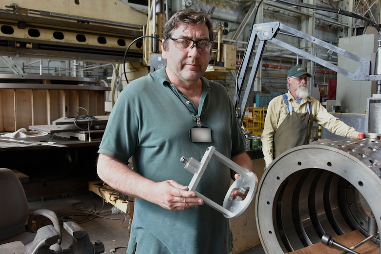 "James ""Trapper"" Landon, an inside machinist in the Arnold Air Force Base Model and Machine Shop, left, shows one of the cages he constructed for the Trapper Lapper 5000, a device developed to speed the lapping process. In the background, Outside Machinist Joel Sizemore puts the Trapper Lapper 5000 to work. The device allows for the automation of a process that previously had to be performed manually. (U.S. Air Force photo by Bradley Hicks) (This image has been altered by obscuring a badge for security purposes)"