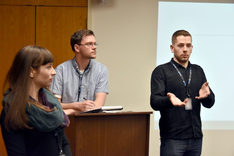 Tyler May, a modeling and simulation engineer with National Aerospace Solutions and president of the NextGen Board of Officers, responds to a question from an attendee of the March 29 NextGen kickoff meeting. NextGen was formed to provide networking and professional development opportunities to new NAS employees. Also pictured are Kassandra Brexel, NextGen networking chair, left, and Garrick Muncie, NextGen treasurer. (U.S. Air Force photo by Bradley Hicks) (This image has been altered by obscuring badges for security purposes)