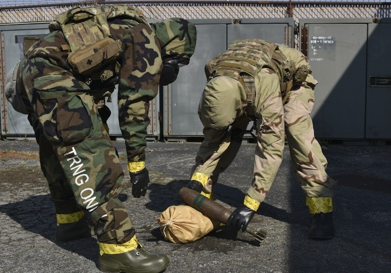 166th Airlift Wing explosive ordnance disposal technician Staff Sgt. Dominic Buckmuse, left, and team leader Staff Sgt. Seth Kohn work to identify an exercise munition at the New Castle Air National Guard Base April 7. A team of three Airmen worked in tandem to practice decontaminating, sealing and transporting potentially hazardous materials. In addition to supporting active duty overseas missions, the 166th EOD Flight supports several local counties. (U.S. Air Force Photo by Capt. Logan Clark)