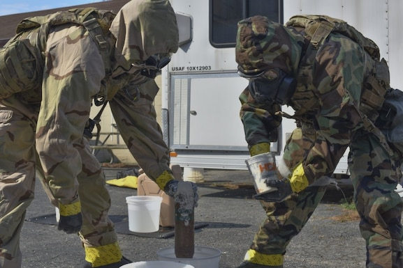 "166th Airlift Wing explosive ordnance disposal team leader Staff Sgt. Seth Kohn, left, and technician Staff Sgt. Dominic Buckmuse, right, seal a suspected ""leaking"" exercise munition at the New Castle Air National Guard Base April 7. A team of three Airmen worked in tandem to practice decontaminating, sealing and transporting potentially hazardous materials. In addition to supporting active duty overseas missions, the 166th EOD Flight supports several local counties. (U.S. Air Force Photo by Capt. Logan Clark)"