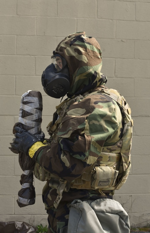 166th Airlift Wing explosive ordnance disposal technician Staff Sgt. Dominic Buckmuse keeps close hold of a decontaminated and sealed exercise munition at the New Castle Air National Guard Base April 7. A team of three Airmen worked in tandem to practice decontaminating, sealing and transporting potentially hazardous materials. These practice munitions are not harmful. In addition to supporting active duty overseas missions, the 166th EOD Flight supports several local counties. (U.S. Air Force Photo by Capt. Logan Clark)