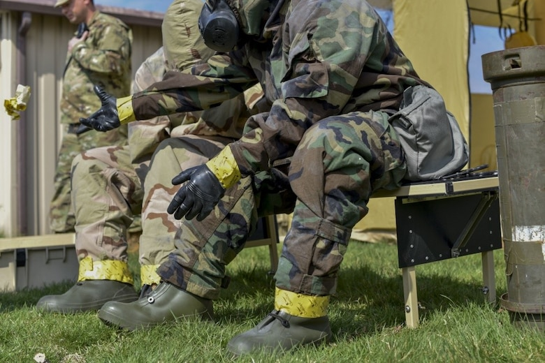 """166th Airlift Wing explosive ordnance technician Staff Sgt. Dominic Buckmuse, right, tosses aside chemical sealing tape as he and Staff Sgt. Seth Kohn begin to remove their """"contaminated"""" chemical gear at the New Castle Air National Guard Base, April 7, 2019. Emergency management Airmen helped a team of three EOD Airmen """"decontaminate"""" their clothing after an exercise to practice decontaminating, sealing and transporting potentially hazardous materials. These practice munitions are not harmful, but Airmen still treat the situation as a realistic training environment. (U.S. Air Force Photo by Capt. Logan Clark)"""