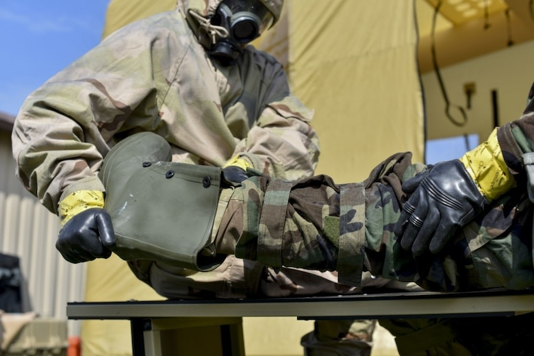 166th Airlift Wing explosive ordnance team leader Staff Sgt. Seth Kohn, left, helps remove the overboot for Staff Sgt. Dominic Buckmuse, right, at the New Castle Air National Guard Base April 7. EOD Airmen work in pairs to decontaminate clothing, as it reduces the chances of contaminating surfaces not exposed to a chemical or biological agent. These practice munitions are not harmful, but Airmen still treat the situation as a realistic training environment. (U.S. Air Force Photo by Capt. Logan Clark)
