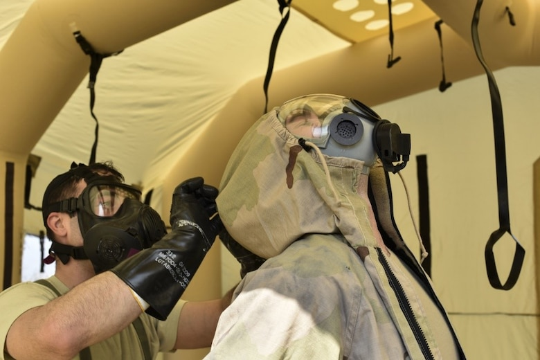 166th Airlift Wing explosive ordnance technician Staff Sgt. Dominic Buckmuse, left, helps remove the protective overcoat of team leader Staff Sgt. Seth Kohn, right, while practicing decontamination procedures at the New Castle Air National Guard Base April 7. EOD Airmen work in pairs to decontaminate clothing, as it reduces the chances of contaminating surfaces not exposed to a chemical or biological agent. These practice munitions are not harmful, but Airmen still treat the situation as a realistic training environment. (U.S. Air Force Photo by Capt. Logan Clark)