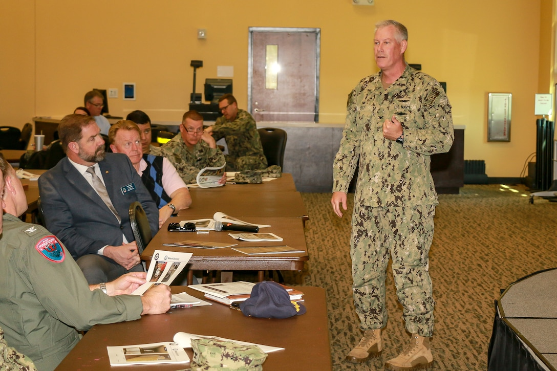 Mike Cannon (seated, second from left in first row), DLA Disposition Services director, listens as Navy Capt. Matthew N. Ott III, commanding officer of the Naval Supply System Command's Fleet Logistics Center at Jacksonville, addresses the audience
