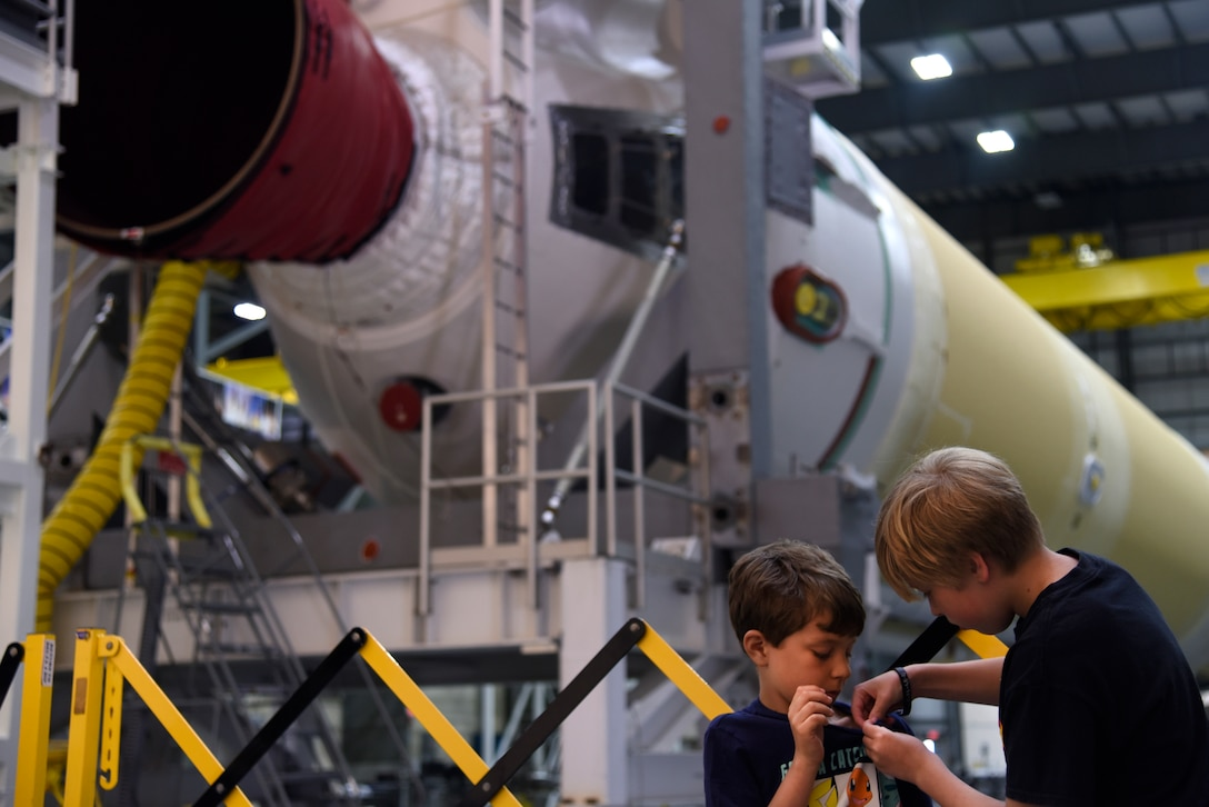 Chase and Seth pin on a minature rocket in front of United Launch Alliance's Delta IV rocket booster during the 45th Space Wing Family Day self guided tour of Cape Canaveral Air Force Station, Fla. on April 6, 2019.