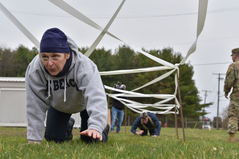 Honorary Commander Ellen McDermott crawls through an Army obstacle course at Joint Base McGuire-Dix-Lakehurst, New Jersey, April 5, 2019.  Members of the Honorary Commander program are able to experience a small taste of military life, showing the training service members have to complete.  (U.S. Air Force photo by 1st Lt. Jaclyn Sumayao)