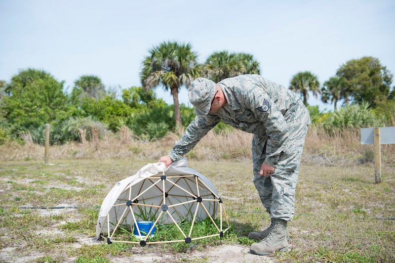 U.S. Air Force Staff Sgt. Derrick C. Johnson, a field test technician assigned to the Systems Development Directorate at the Air Force Technical Applications Center, Patrick Air Force Base, Florida, lifts the fabric from a small geodesic dome he developed to collect hydroacoustic data. (U.S. Air Force photo by Matthew S. Jurgens)
