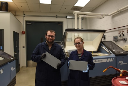 Chemist Dr. Kylee Fazende (right) and Engineer Dr. Charles White hold test-ready paint panels in Naval Surface Warfare Center Carderock Division's accelerated exposure and weathering lab in West Bethesda, Md., on April 4, 2019. (U.S. Navy photo by Edvin Hernandez/Released)