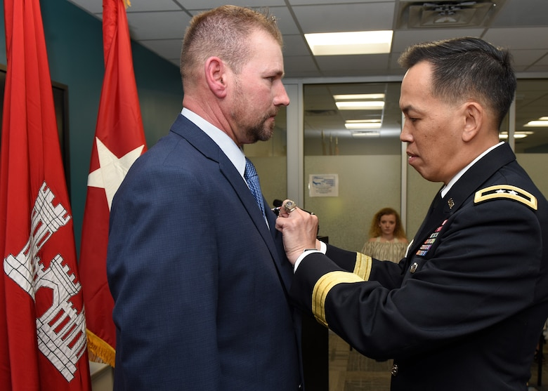 Maj. Gen. Mark Toy, U.S. Army Corps of Engineers Great Lakes and Ohio River Division commander, presents the Secretary of Defense Medal for the Defense of Freedom April 8, 2019 to Billy Johnson, recognizing the severe injuries he sustained while supporting a Corps of Engineers mission as a security officer in Iraq Dec. 9, 2007. The general presented the medal on behalf of Secretary of the Army Mark T. Esper during a ceremony held at the Tennessee Valley Authority Central Labs near Chickamauga Lock in Chattanooga, Tenn. (USACE photo by Lee Roberts)