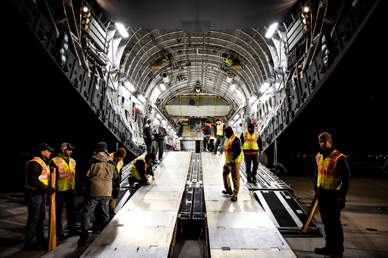 Men in transport jet's cargo bay.