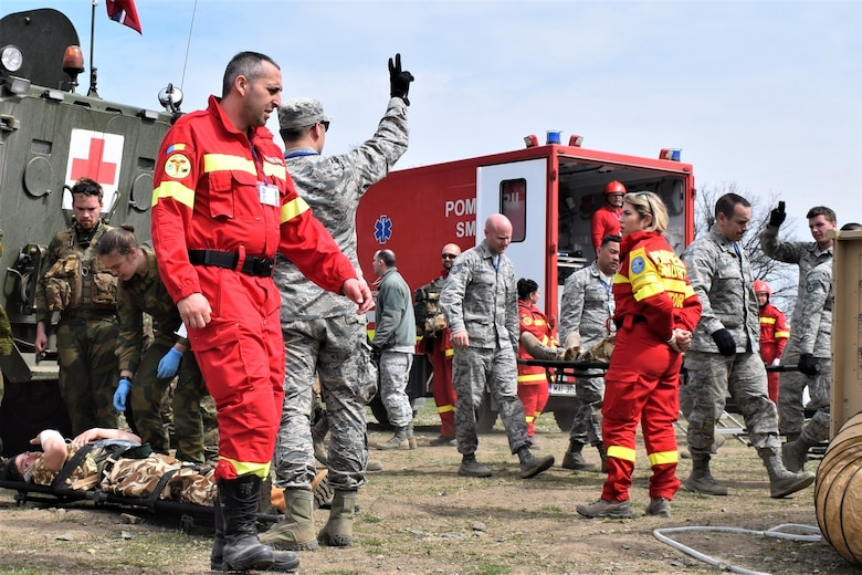 Civilian first responders from Romania participate along with Airmen from the 86th Medical Group, Ramstein Air Base, Germany, in a multinational medical exercise drill during Vigorous Warrior 19, Cincu Military Base, Romania, April 8, 2019. Vigorous Warrior 19 is NATO's largest-ever military medical exercise, uniting more than 2,500 participants from 39 countries to exercise experimental doctrinal concepts and test their medical assets together in a dynamic, multinational environment. (U.S. Air Force photo by 1st Lt. Andrew Layton)