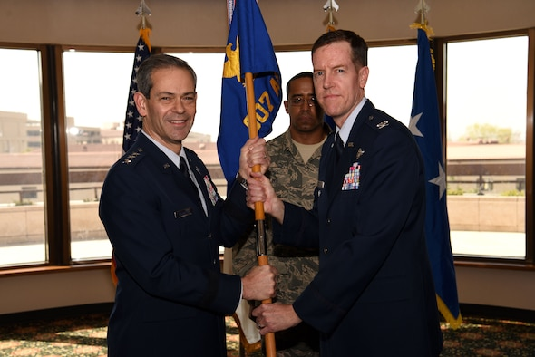 U.S. Air Force Lt. Gen. Kenneth S. Wilsbach, Seventh Air Force commander, passes the 607th Air Operations Center guidon to Col. Christopher Russell, incoming commander, during an assumption of command ceremony at Osan Air Base, Republic of Korea, April 5, 2019. The passing of the guidon symbolizes a change of leadership and responsibility. (U.S. Air Force photo by Staff Sgt. Kelsey Tucker)
