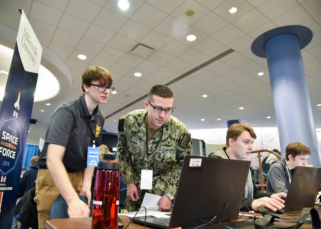 Greg Bodmer, Cryptologic Technician (Networks) assigned to Cyber Defense Activity - 64, Fort Meade, Md., examines a participants monitor during the 14th Annual Mid-Atlantic Collegiate Cyber Defense Competition Regional Finals, March 29, 2019 at Johns Hopkins University Applied Physics Laboratory, Laurel, Md. Each year all participants are divided into three teams with specific responsibilities. (U.S. Air National Guard photo by Staff Sgt. Enjoli Saunders)