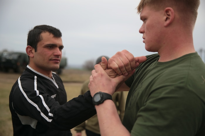 A U.S. Marine with Special Purpose Marine Air-Ground Task Force-Crisis Response-Africa 19.1, Marine Forces Europe and Africa, demonstrates Marine Corps Military Martial Arts Program techniques to a soldier with the Georgian army's 12th Infantry Battalion during Platinum Eagle 19.1, a multilateral training exercise held at Babadag Training Area, Romania, March 16, 2019.