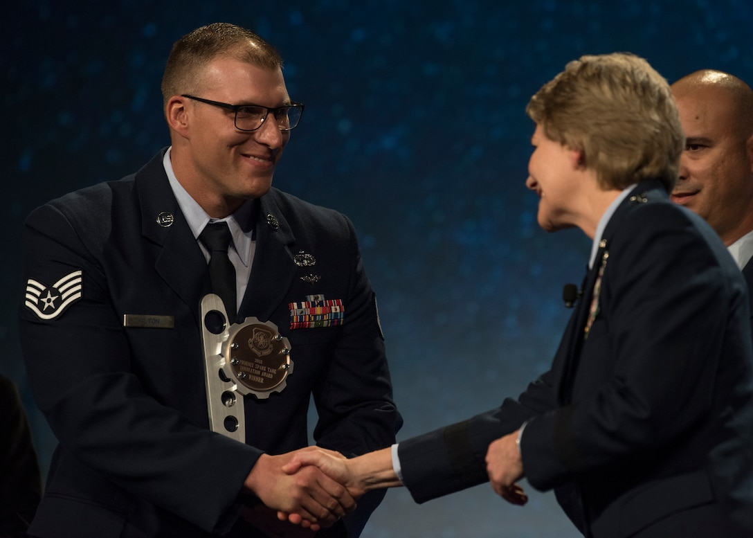 Gen. Maryanne Miller, Air Mobility Command commander, congratulates the winner of the 2018 AMC Phoenix Spark Tank competition, Staff Sgt. Travis Alton from the 19th Logistics Readiness Squadron, during the Airlift/Tanker Association Symposium in Grapevine, Texas, Oct. 27, 2018.