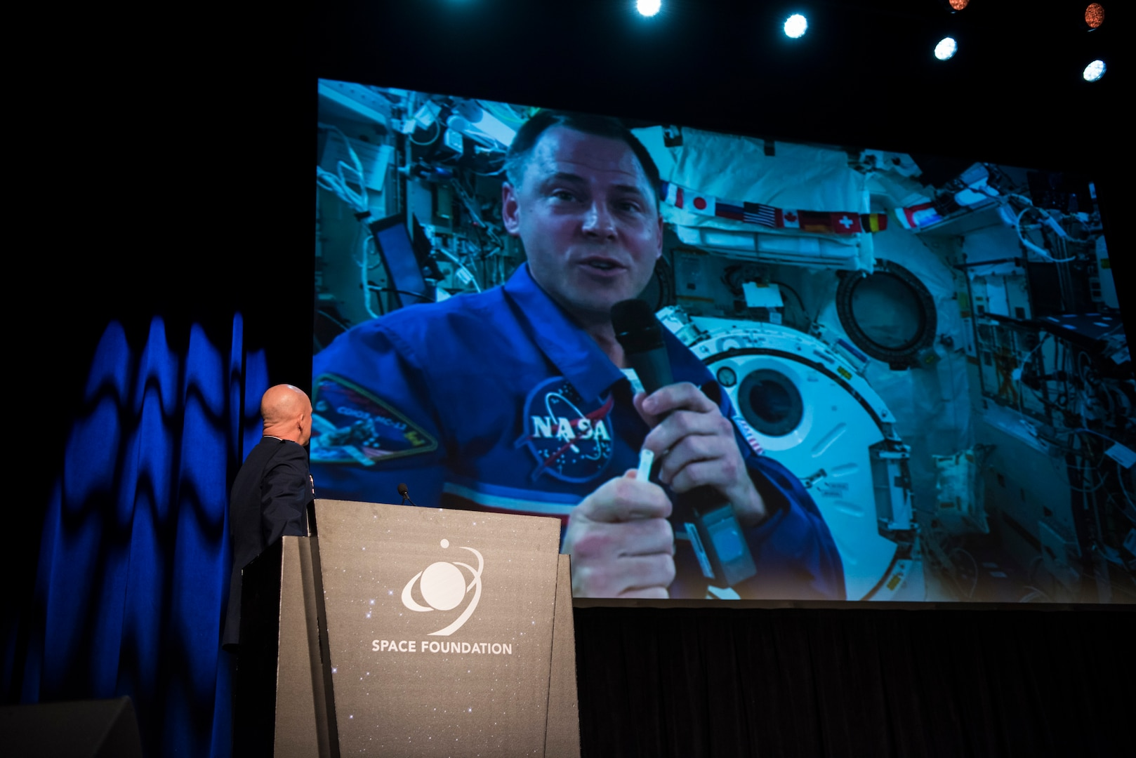 Gen. Jay Raymond, commander of Air Force Space Command and the Joint Force Space Component Command, surprises an audience at the 35th Space Symposium with a live video feed from the International Space Station featuring Air Force Col. Nick Hague, NASA Astronaut, in Colorado Springs, Colo., April 9, 2019.