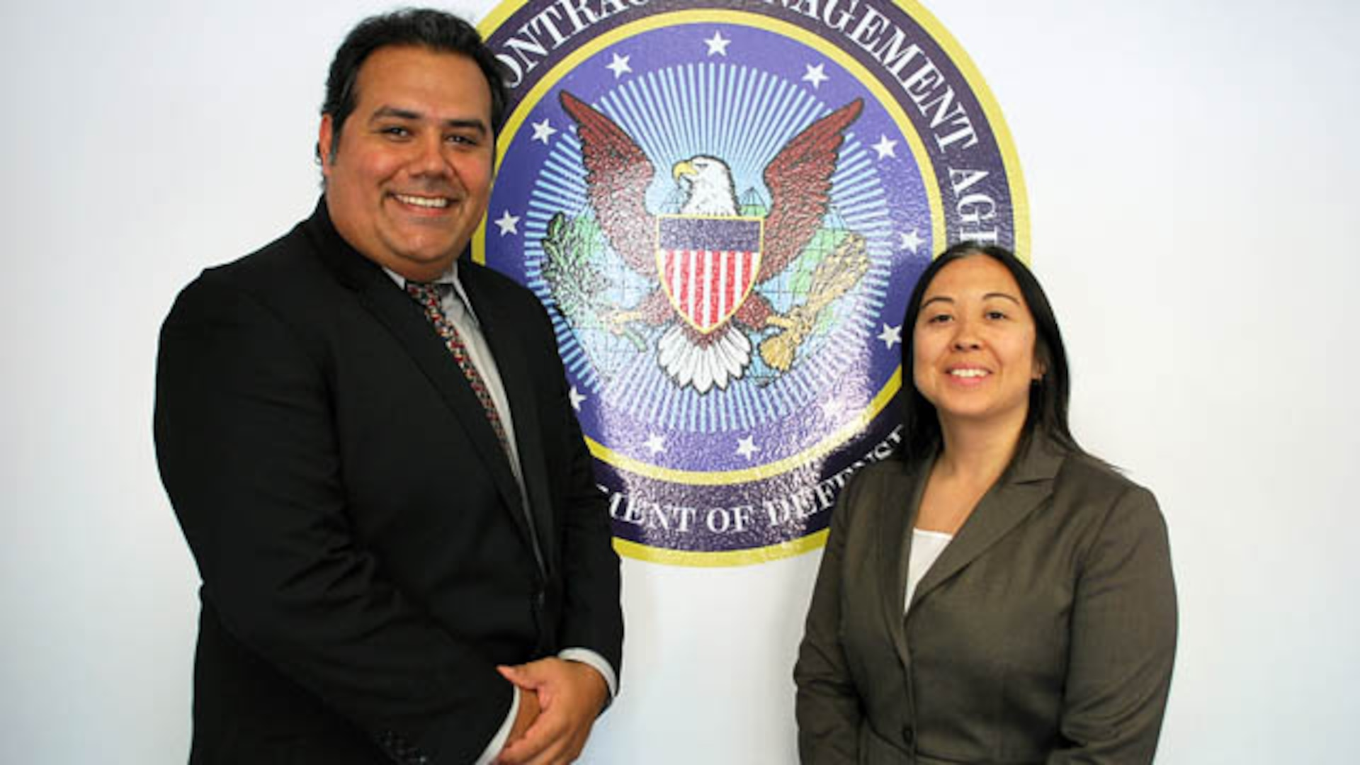 A man and a woman stand in front of Agency seal.