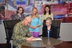DLA Distribution Commanding Officer Navy Rear Adm. Kevin M. Jones and Deputy Commander Twila C. Gonzales, Senior Executive Service, sign the 2019 Sexual Assault Awareness Proclamation in the presence of Distribution Sexual Assault Response Coordinator A.J. Byerly (top center) and Family Advocacy Interns from Messiah College, Katie Campbell and Ally Bishop (left and right, respectively) April 2.