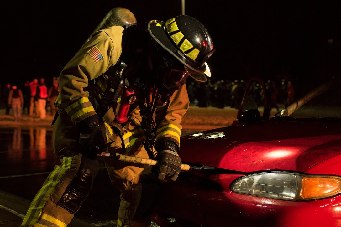 A firefighter assigned to Little Rock Air Force Base, Arkansas, practices dousing a car fire during Operation Phalax held March 30-31, 2019.  The operation is a joint exercise hosted by the Arkansas National Guard for civil and military organizations to train their members in tactics and techniques used in responding to a civil disturbance. (U.S. Air National Guard photo by Staff Sgt. Matthew Matlock)