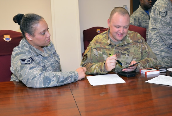 Staff Sgt. Luz Trice, 433rd Mission Support Group command support staff, guides Staff Sgt. Daryn Kline, 433rd Aircraft Maintenance Squadron avionics specialist, through the process of submitting a travel voucher by using the new mobile common access card enabled Air Force Connect app at Joint Base San Antonio-Lackland, Texas April 7, 2019.