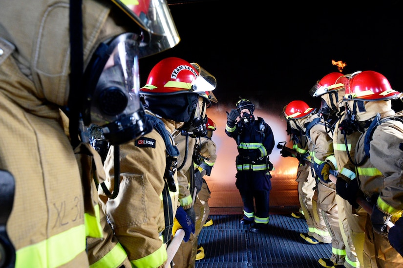 Sailors put out a fire during firefighting training.