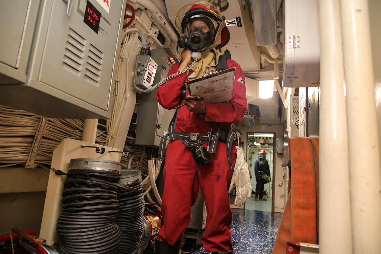 A sailor dressed in firefighting gear communicates via radio aboard a ship.