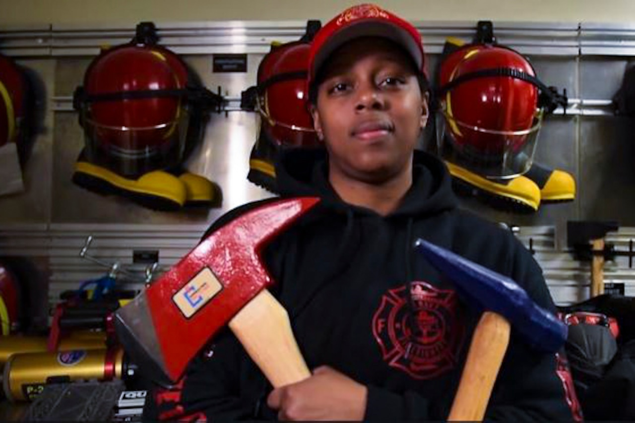 A sailor poses for a photo holding an ax and a hammer while standing in front of a wall of hanging firefighter helmets and boots.