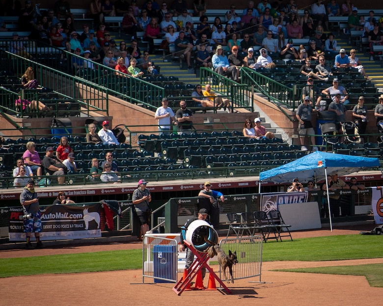 Spectators watch as a working dog and its handler work through an obstacle at the 2019 Desert Dog Trials, April, 6, at Scottsdale Stadium, Scottsdale, Ariz.